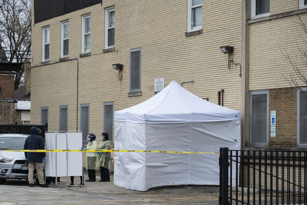 Chicago Department of Public Health workers set up a tent outside Vaughn Occupational High School.