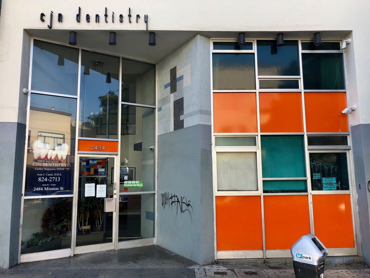 The exterior of CJN Nogueiro Dentistry in San Francisco. The facade has glass and orange panels.