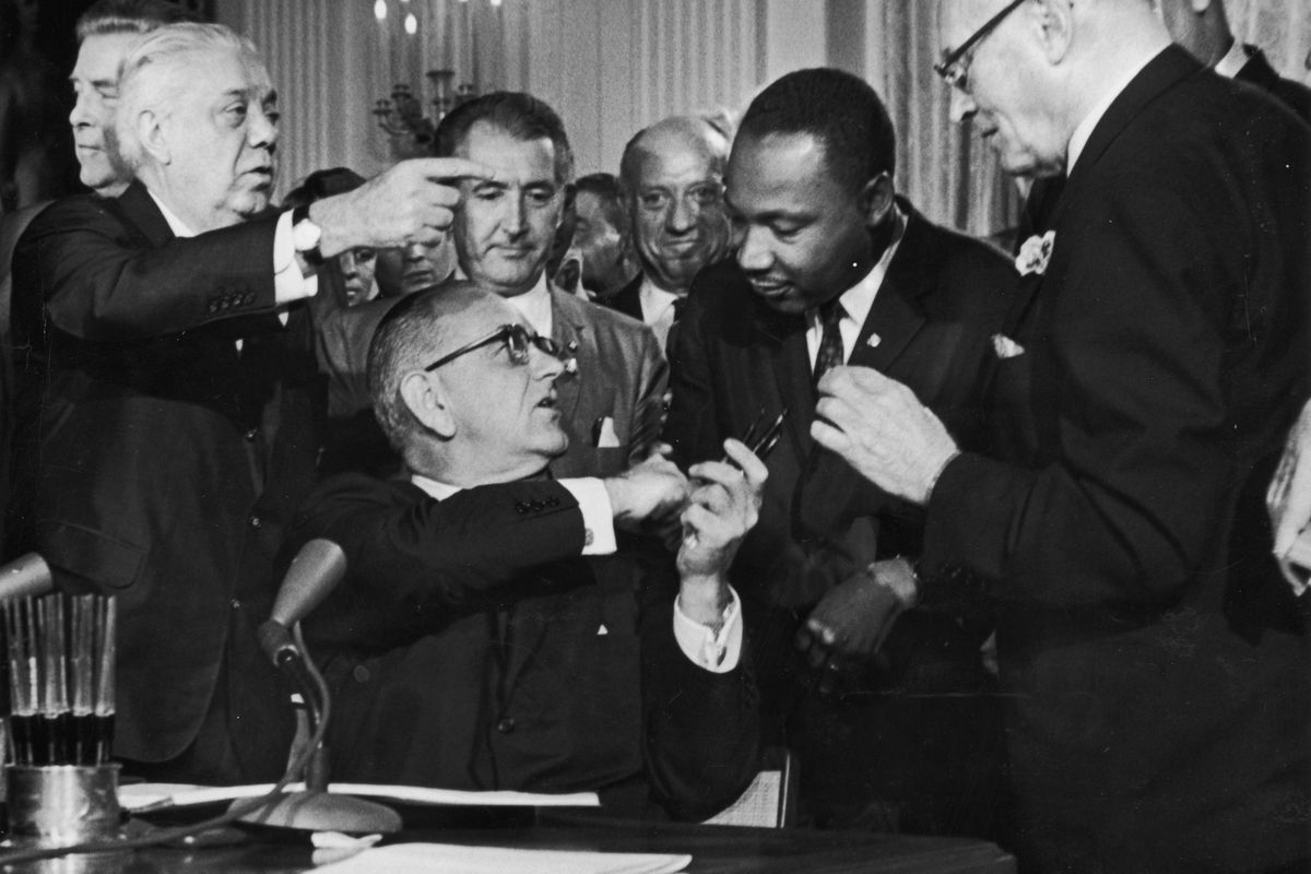 President Johnson shakes Martin Luther King, Jr.'s hand at the signing of the 1964 Civil Rights Act