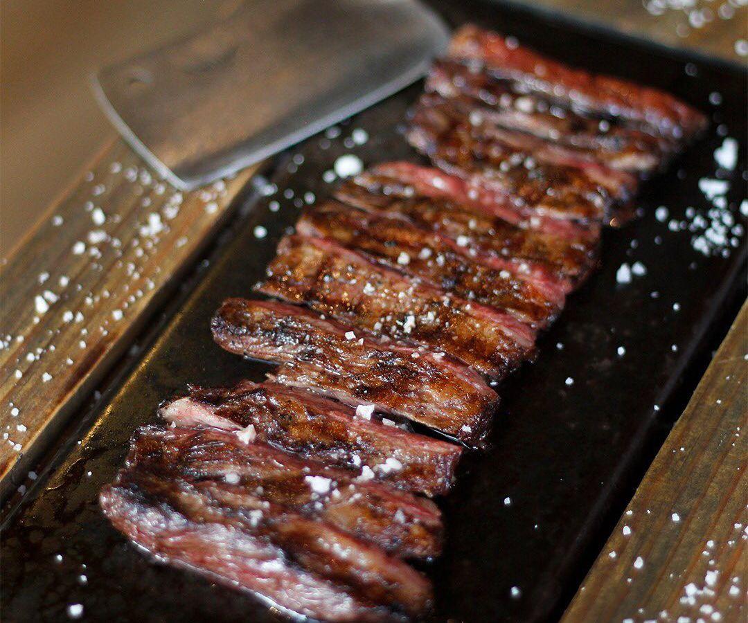 A sliced hanger steak is seasoned with salt
