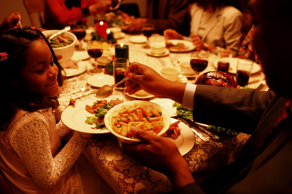 Black family has festive Christmas dinner. Father serves daught, grandparents and child enjoy holiday meal at home.