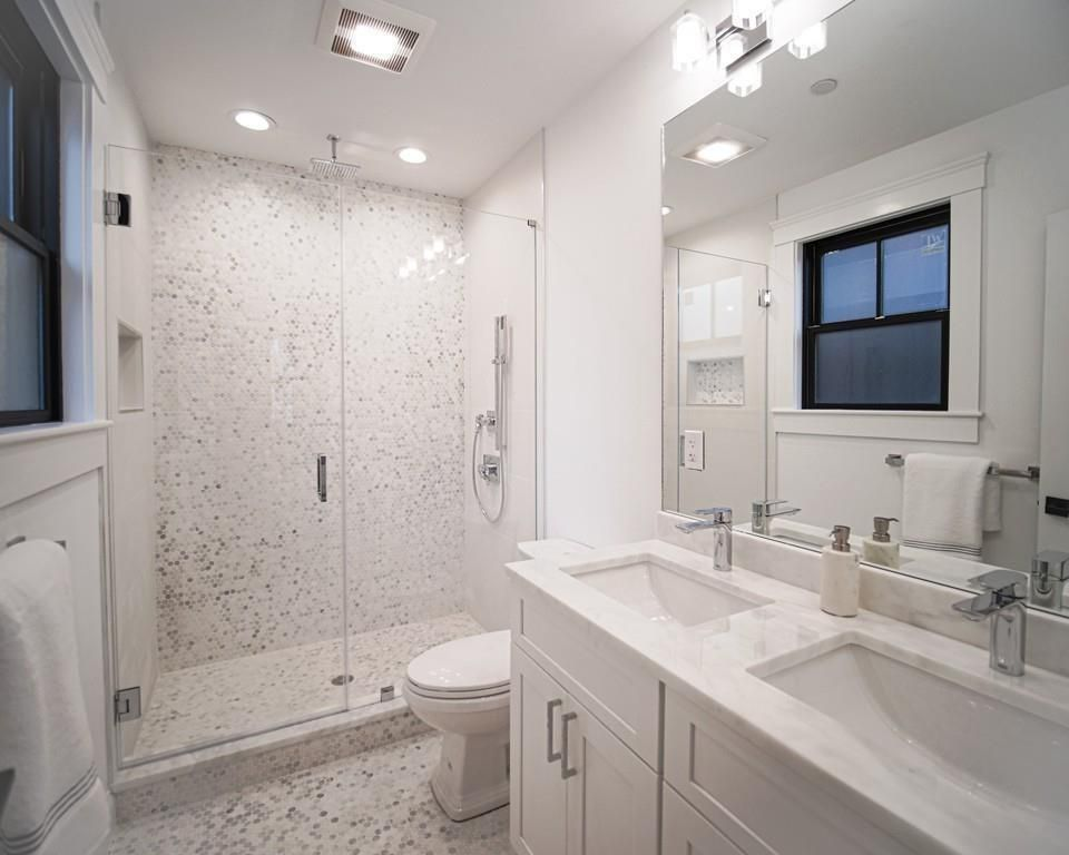 A bathroom with two sinks and a shower with a glass door.