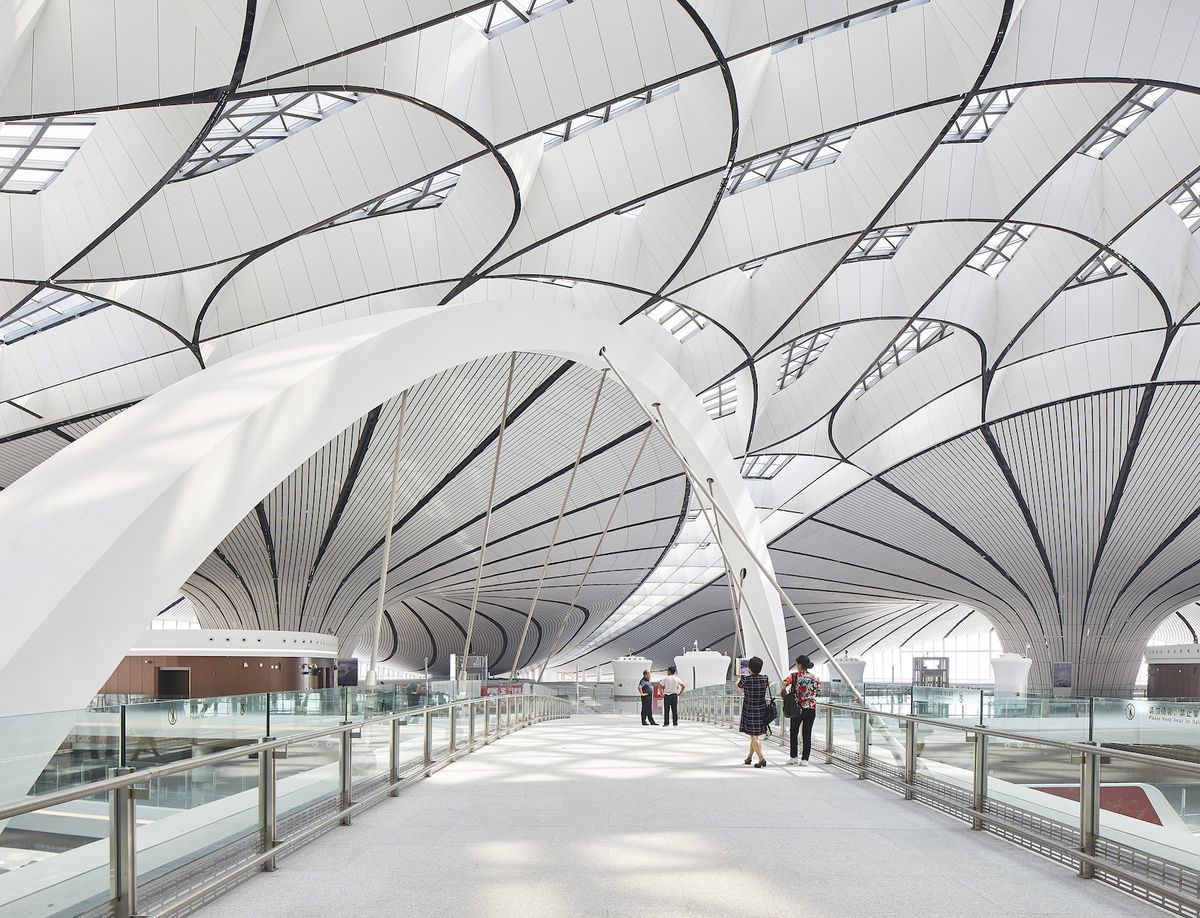 People walking down corridor under geometric ceilings.