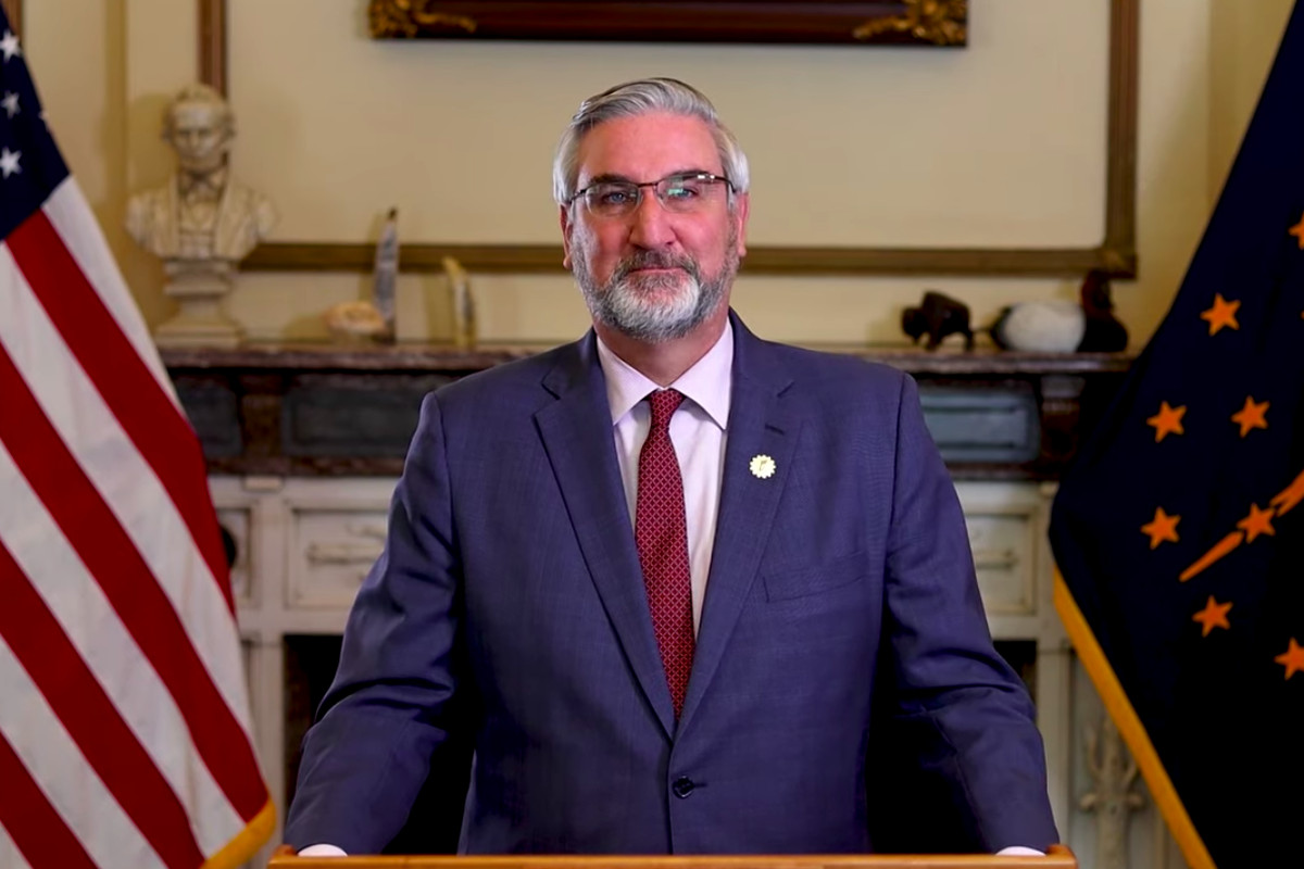 Gov. Eric Holcomb between two flags.