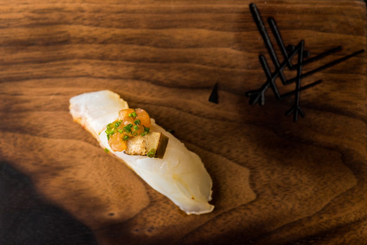 The Robin logo alongside seared canary rockfish, its liver, grapefruit ponzu, and chives