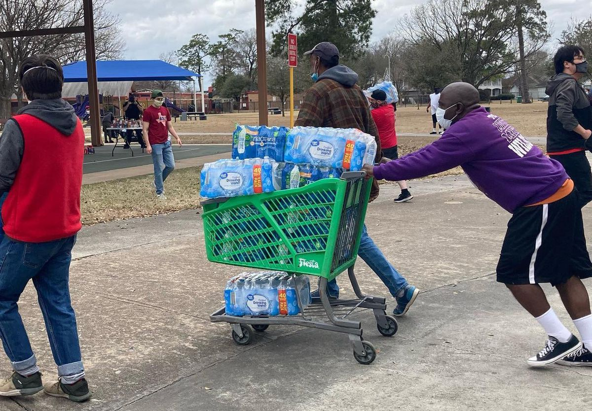 A Black man in a purple hoodie and black shorts pushed a green grocery cart filled to the brim with cases of bottled water at a distribution site in Houston