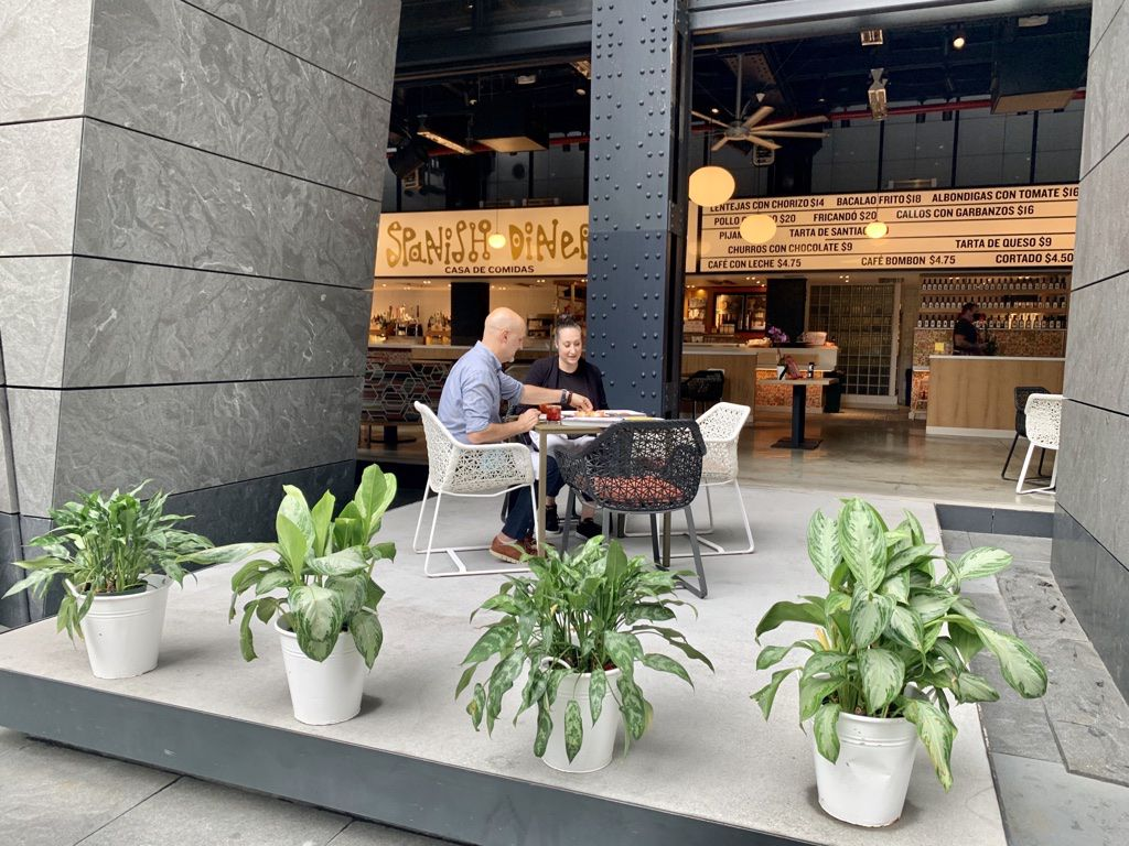 Two people sitting outside at a table on a grey stone patio with potted green plants in the foreground