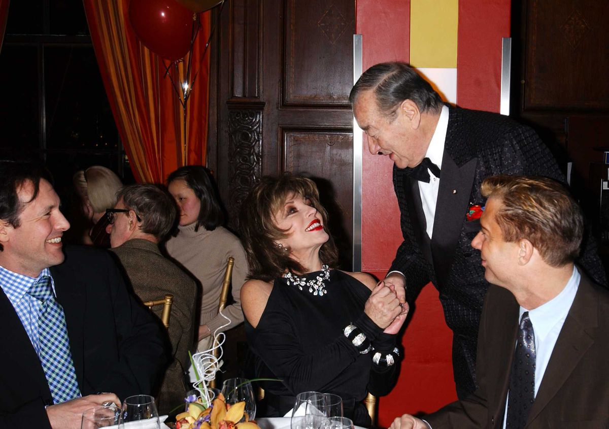 Actress Joan Collins and her boyfriend Percy Gibson (L) chat with LeCirque Restaurant owner Sirio Maccioni December 31, 2001 at a New Years Eve dinner party in New York City.