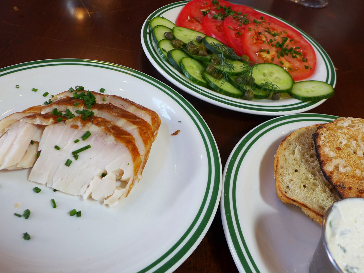 On three separate plates, sliced fish, vegetables, and a bagel with cream cheese served in a separate metal cup.