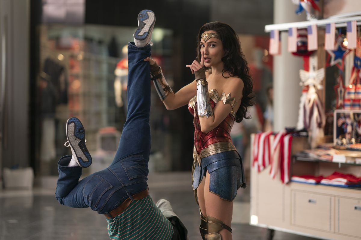 """Gal Gadot as Wonder Woman holds a man upside down by his ankle while holding a finger to her lips in a """"shhh"""" gesture in Wonder Woman 1984."""