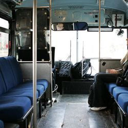"""Jacquline Stuart, right, laughs with her boyfriend Tyson Lloyd, left, as he drives the 8th East Express bus line for Utah State University. """"I think it would be silly to go live in a tent to save money,"""" Stuart said."""