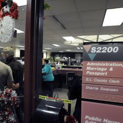 Couples get their marriage licenses processed inside the Salt Lake County clerk's office after a federal judge ruled that Amendment 3, Utah's same-sex marriage ban, is unconstitutional on Friday, Dec. 20, 2013.