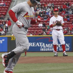 St. Louis Cardianls Carlos Beltran runs to home plate after he hit a home run in the first inning of their baseball game in Cincinnati Tuesday April 10, 2012. Looking on is Cincinnati Reds pitcher Mike Leake who gave up the home run.