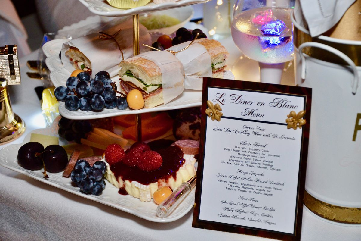 menu and tiered serving plate with sandwiches, grapes, and pastries