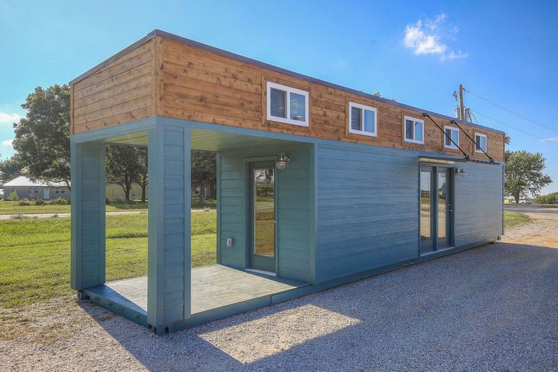 A shipping container house is teal with a row of windows on the top 1⁄4 of the home. A front porch has been carved out and there is a single door that lets you enter.