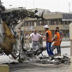 Baghdad municipality workers clean up after a car bomb attack in  Palestine Street, Baghdad Iraq, Thursday, April 19, 2012. A wave of morning bombings across several cities on Thursday, killing and injuring dozens of Iraqis, police said, shattering weeks of calm in a reminder of the nation's continued insurgency. (AP Photo/Hadi Mizban)