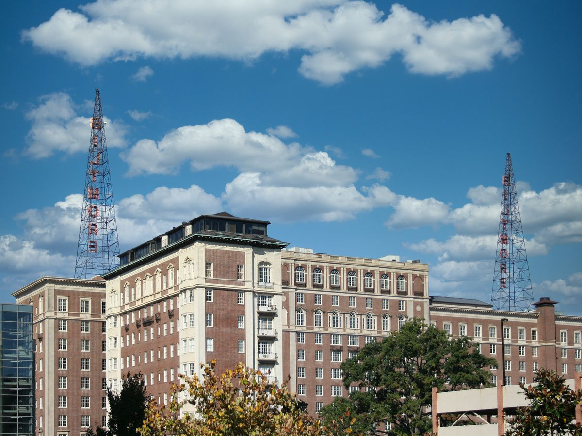 Multi-story building with twin radio towers on the roof.