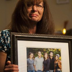 Susan Hunt holds a photo of her family, including her son, Darrien Hunt, who was killed by police Wednesday, at her home in Saratoga Springs, Friday, Sept. 12, 2014.