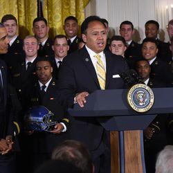 U.S. Naval Academy head football coach Ken Niumatalolo speaks at the White House during a presentation of the Commander-In-Chief's Trophy. President Barack Obama stands at left.