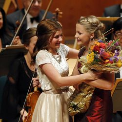 Karen Lela Ferry, right, receives flowers from Caroline Richards after performing during the 55th annual Salute to Youth concert in Salt Lake City Tuesday, Sept. 30, 2014.