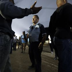 Security guard Jose Sanchez checks concert goers on his first day back at a large event since he worked during last Sunday's mass shooting Friday, Oct. 6, 2017, on the outskirts of Las Vegas. Sanchez and his colleagues at a private security firm manning the Route 91 Harvest music festival Sunday night in Las Vegas were a force of 200 unarmed first responders who helped people exit amid the panic. Despite the fresh trauma and losing one of their own, many of the company's guards are returning to work events for the first time again this weekend. (AP Photo/Gregory Bull)