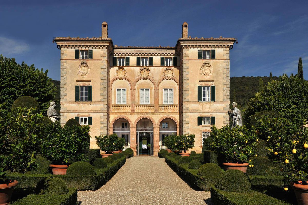Three-story yellow-stucco villa with arched entryways and a manicured garden in the front.