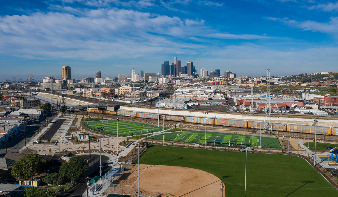 An aerial view of Albion Riverside Park in Los Angeles, California. In the foreground is a ball field. In the distance are many city buildings.