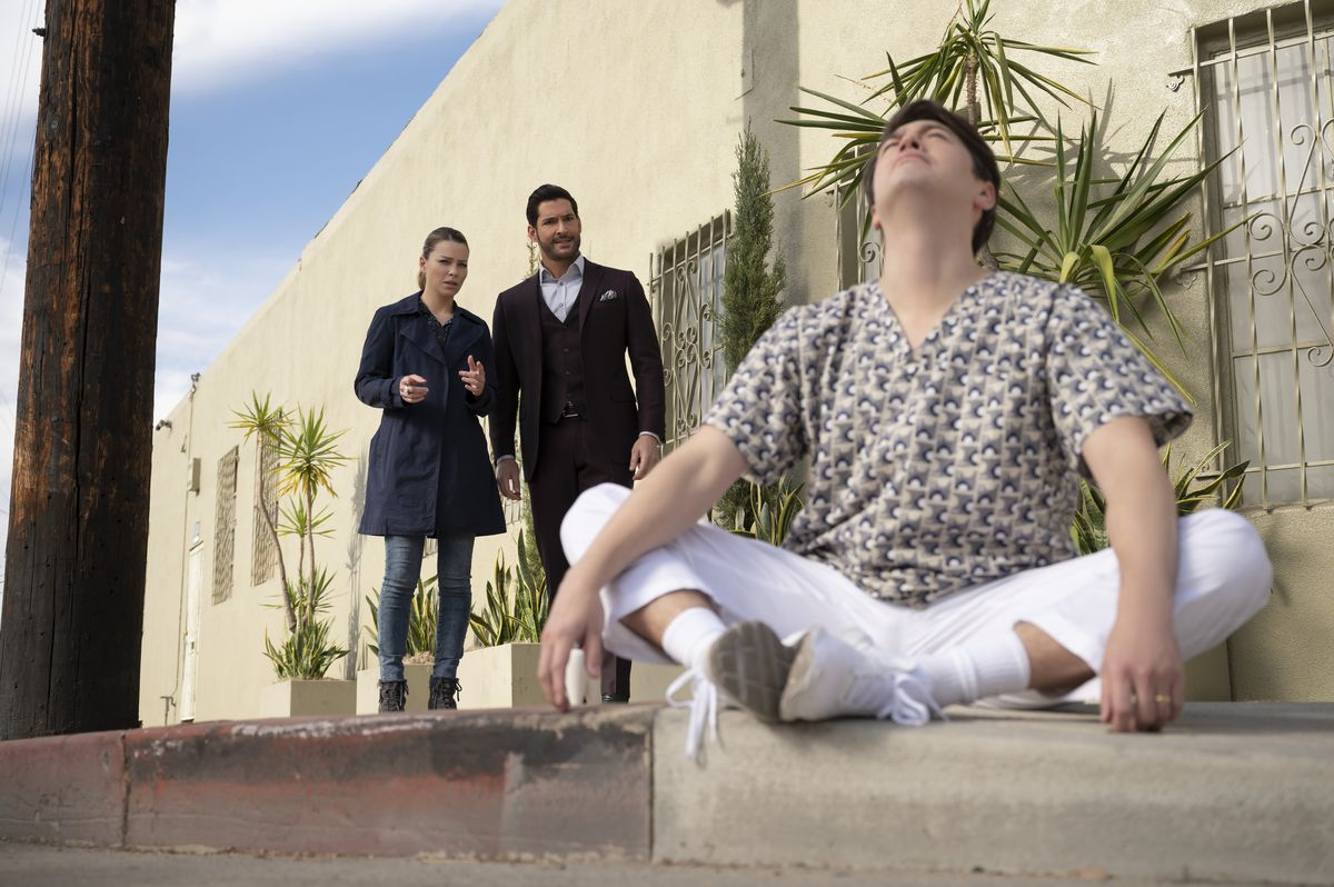 Lauren German and Tom Ellis as Chloe and Lucifer approach a man sitting in lotus position with his eyes closed in season 6 of Lucifer