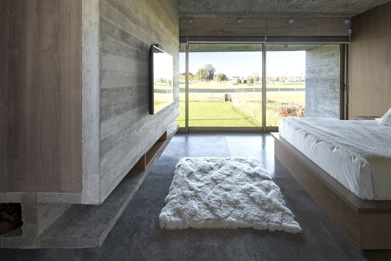 Bedroom with concrete floor and sheepskin rug.