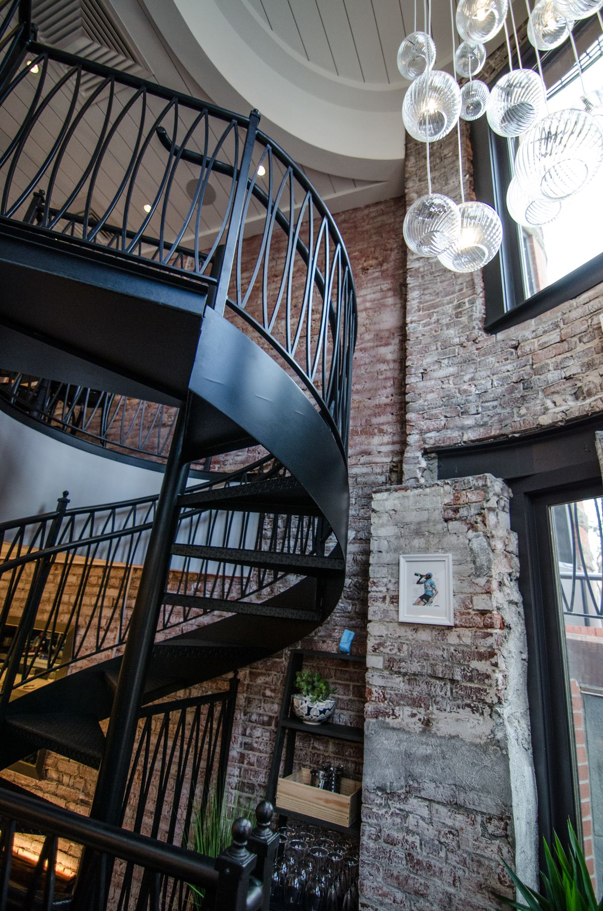 A black spiral staircase spans two floors of a restaurant, with white-washed brick walls in the background and a dangling light fixture made of glass globes.