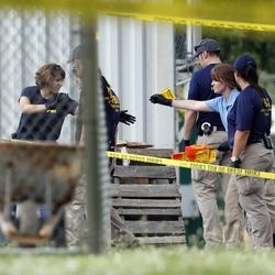 Investigators hand off an evidence flag around the baseball field in Alexandria, Va., Wednesday, June 14, 2017, that was the scene of a shooting where House Majority Whip Steve Scalise of La., and others, were was shot during a congressional baseball practice.