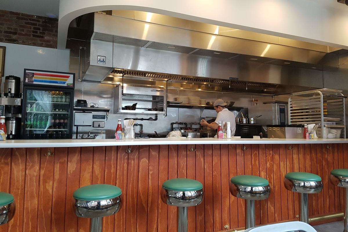 Green bar stools are located in front of a wooden diner counter, and the kitchen can be seen in the background