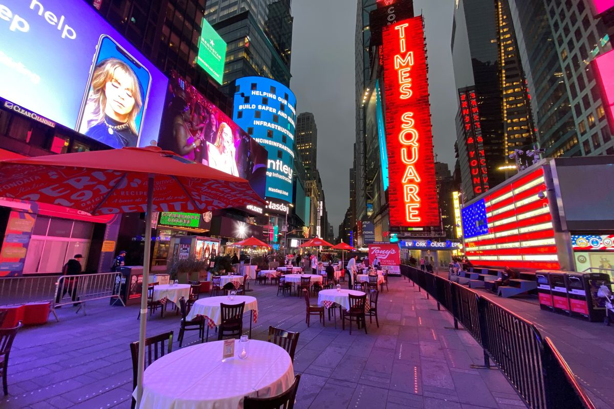 Times Square billboards are lit up in the background with tables and chairs placed in a cordoned off area