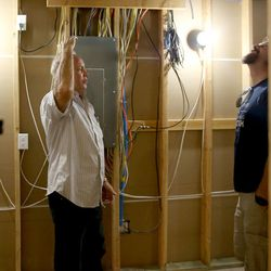 Construction manager Rick Groendyke and homebuyer David Wilk discuss the energy recovery ventilator in an energy-efficient home in Sandy on Friday, Aug. 12, 2016. Utah is one of only 10 states in the nation that allow energy ratings to be part of updated residential building codes so consumers can see if the home they are about to buy will be efficient and save them money on their utility bills.