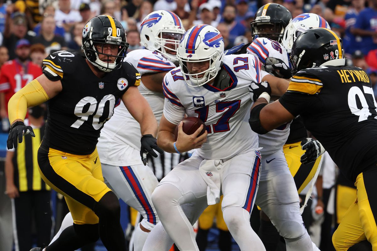 Josh Allen #17 of the Buffalo Bills is pursued by Cameron Heyward #97 and T.J. Watt #90 of the Pittsburgh Steelers at Highmark Stadium on September 12, 2021 in Orchard Park, New York.