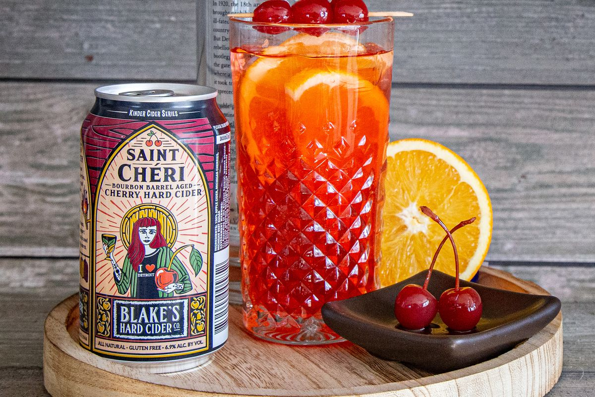 Saint Cheri cider in a red can next to a glass of cherry cider and a plate with two maraschino cherries.