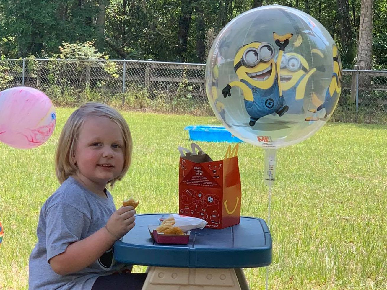 4-year-old Aydan munches on a birthday lunch of a McDonald's happy meal. Later on, neighbors would flood his street with birthday wishes and balloons to celebrate a most unusual birthday.