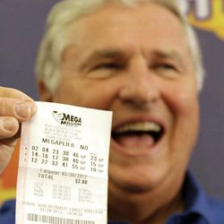 Merle Butler, of Red Bud, Ill., holds up his winning lottery ticket during a news conference at the Red Bud Village Hall on Wednesday, April 18, 2012, in Red Bud, Ill. The retired southern Illinois man and his wife have claimed the third and final share of last month's record $656 million Mega Millions jackpot.