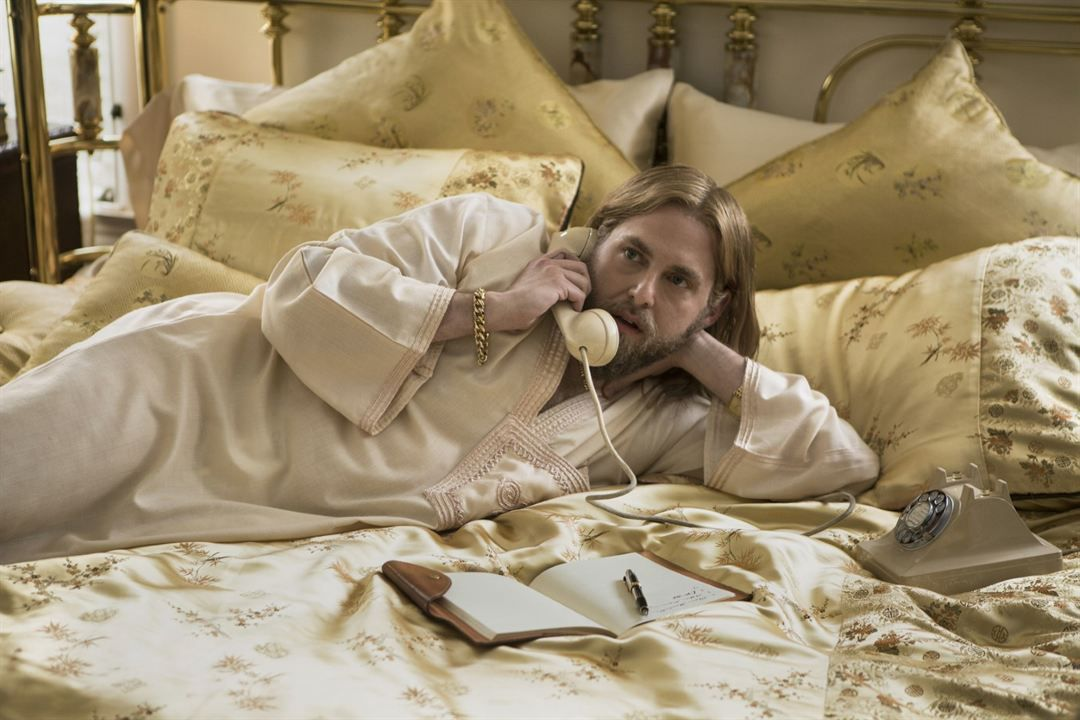 Jonah Hill wearing a satin robe as he lounges horizontally on a bed and talks on a corded phone