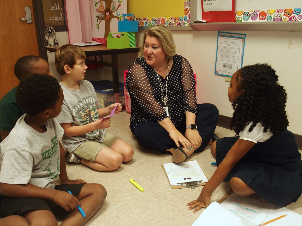 Jennifer Chandler, the district's CLUE supervisor, sits with students in a gifted education class at White Station Elementary.