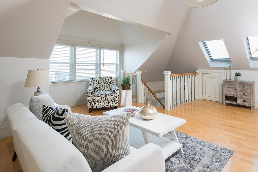 A sunny living room at the top of some stairs.