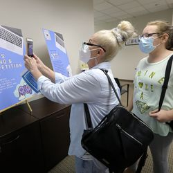Pam Chudomelka uses her phone to scan a QR code that leads to a link where eighth grader Cheyanne Fizer can sign up for extracurricular activities during in-person orientation at Mountain Heights Academy, an online school based in West Jordan, on Tuesday, Aug. 24, 2021.