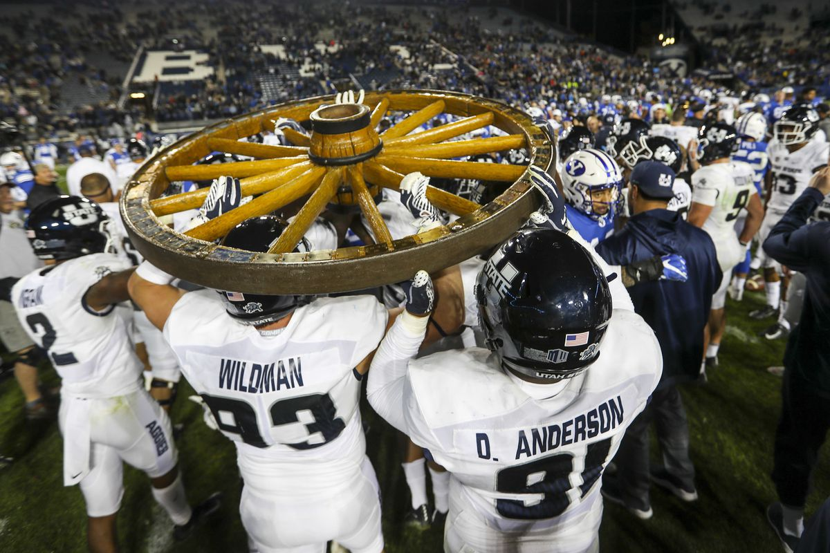 The Utah State Aggies carry the Old Wagon Wheel to midfield after defeating the Cougars and retaining the wheel at LaVell Edwards Stadium in Provo on Friday, Oct. 5, 2018.