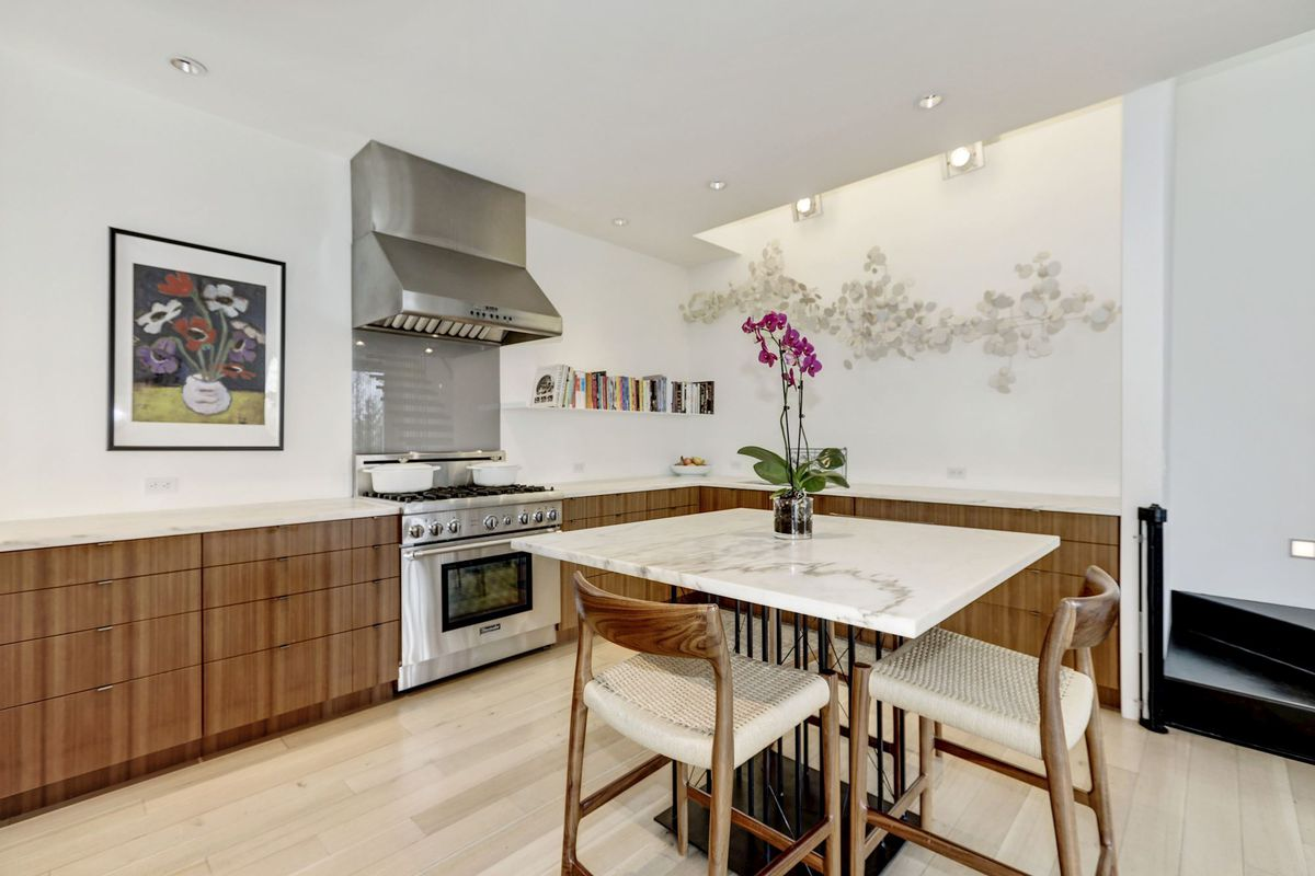 A kitchen with white counters, stainless steel stove, and wooden cabinets.