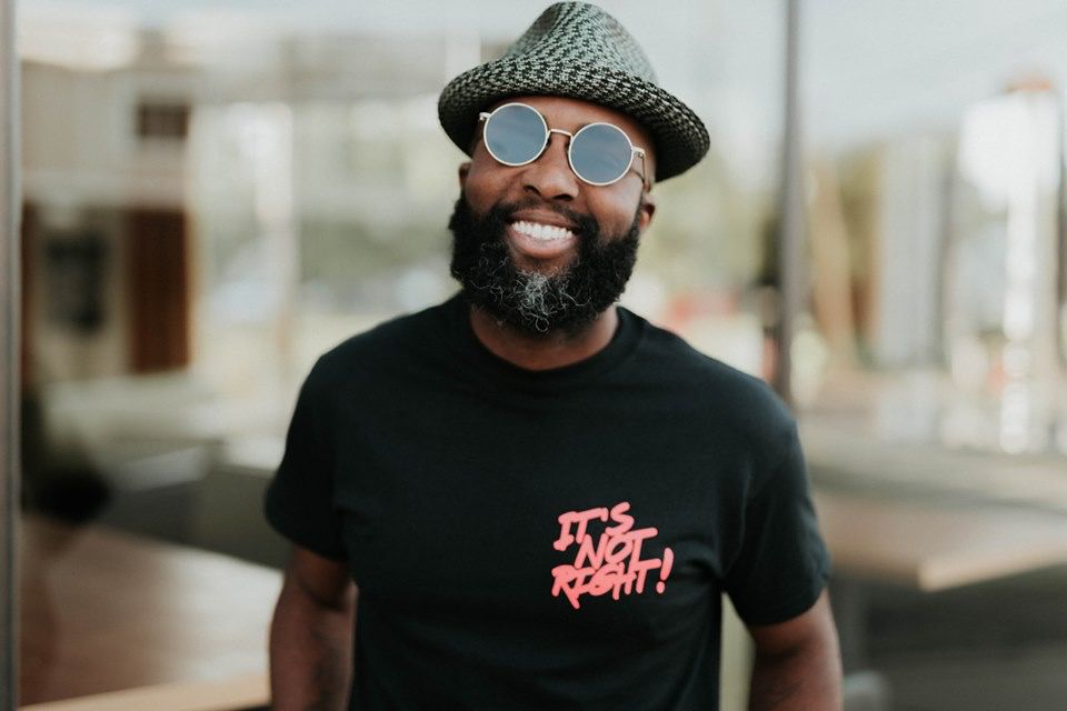 """Tracy Evans, a man with a beard, smiles at the camera wearing a hat, round-framed sunglasses, and a black shirt with pink writing reading """"It's Not Right."""""""