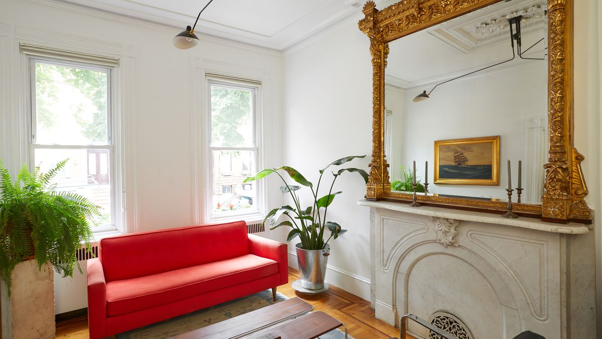 A living area. There is a bright red couch and a fireplace. Above the fireplace sits a large mirror with an ornamental brass frame. There are two windows letting in natural light. There are houseplants in planters on the floor and a wooden coffee table.