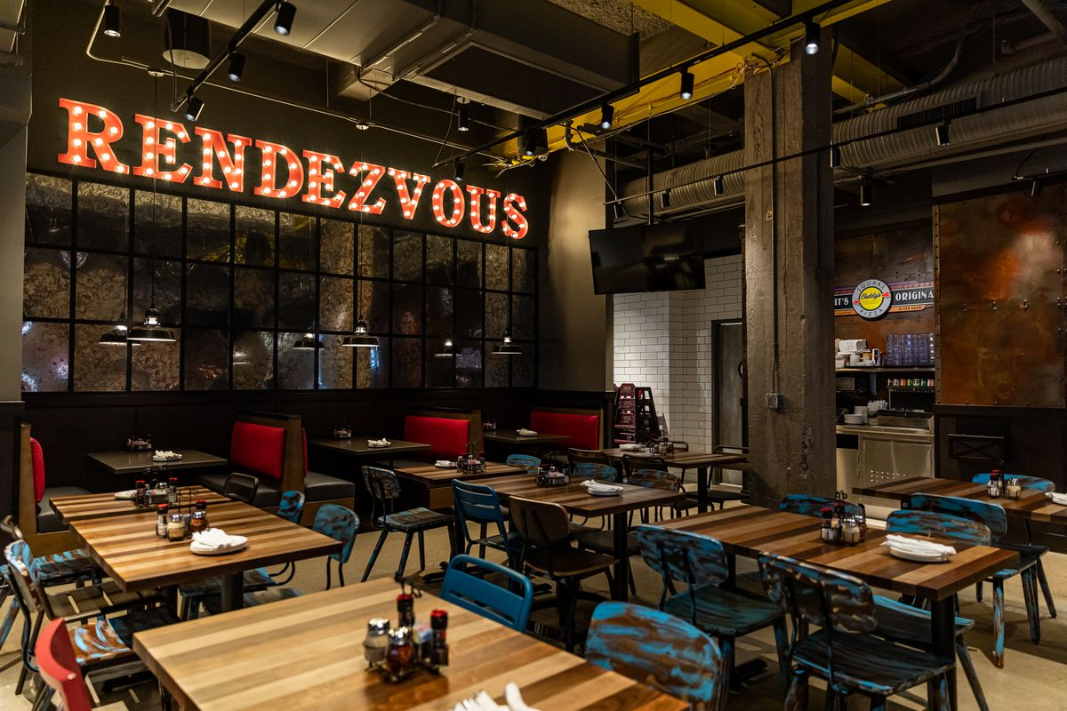 """A light up sign reading """"Rendezvous"""" runs along a wall inside the dining room at Buddy's Pizza's downtown restaurant."""