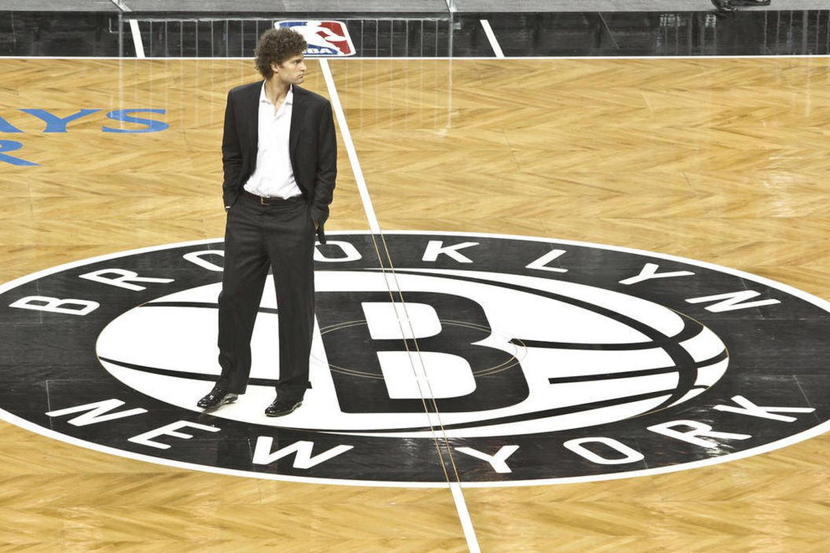 Brooklyn Nets basketball player Brook Lopez walks onto the floor of the Barclay's Center, Brooklyn's newest arena and the team's new home, after a ribbon cutting ceremony on Friday, Sept. 21, 2012 in New York. The ceremony marked the official unveiling of