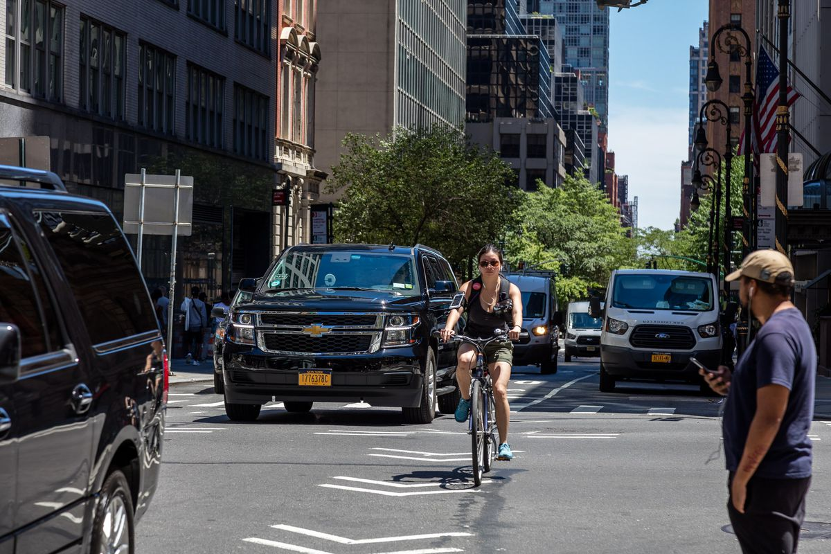 A woman rides a bicycle on a Manhattan street during the day, and is surrounded by cars on both sides.