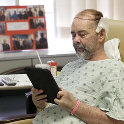 In this photo taken on Wednesday, June 3, 2015, James Boysen reads messages in his hospital bed at Houston Methodist Hospital, in Houston. Boysen received the world's first skull and scalp transplant to help heal a large head wound from cancer treatment.